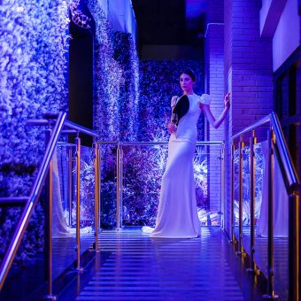 Vista de noche de una novia en el jardín vertical de Mestura Restaurante