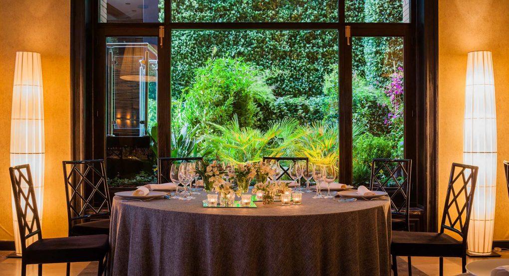 Montaje de una mesa en el salón de bodas de Mestura con el jardín vertical de fondo