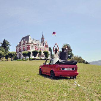 Novia lanzando el ramo junto al novio, montados en un coche dirigiéndose al Palacio de la Concepción en Gijón