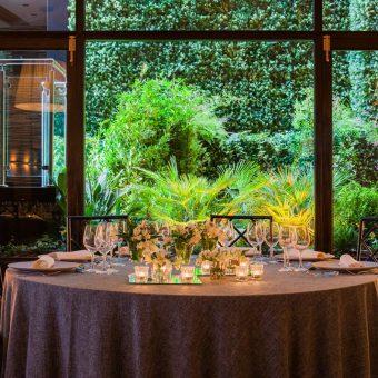 Montaje de una mesa en el salón de bodas con el jardín vertical de fondo