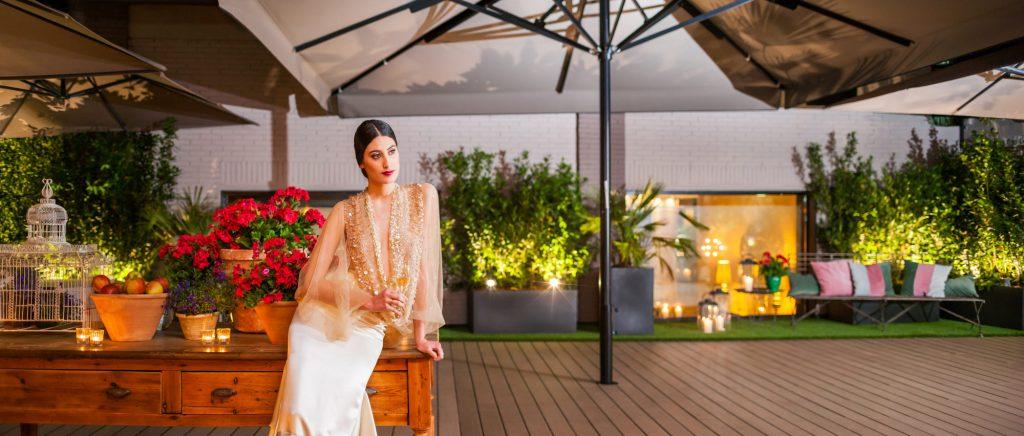 Novia apoyada en una mesa, sosteniendo una copa en la terraza de Mestura Restaurante